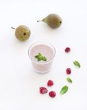 Glass of raspberry and pear smoothie with fresh. Mint leaves on white backdrop Stock Photos