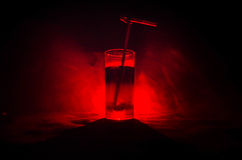 Glass of Red Alcoholic Cocktail on Dark Background with smoke and backlight. Fire hot coctail. Club concept Stock Photography
