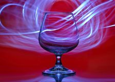 Glass on a red background with lines of light in the background stock photos