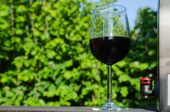 A glass of red Bag-in-Box wine. A glass of red wine and a crane at a Bag-in-Box outdoors in a sunny garden royalty free stock photography