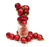 Glass with red Christmas balls over white background Stock Photo