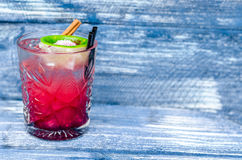 A glass of red cocktail with ice, lime and straw, on a blue denim background. Side view Royalty Free Stock Photography
