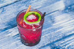 A glass of red cocktail with ice, lime and straw, on a blue denim background. View from above stock image