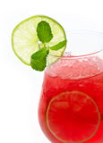 Glass of red cocktail with lime slices Stock Photo
