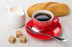 Red cup with coffee, spoon, sugar, bread, jug of milk. Glass red cup with coffee, spoon on saucer, sugar cubes, bread, jug of milk on wooden table Royalty Free Stock Photography