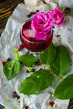 A glass with a red drink with berries, ice and a pink flower on stock photos