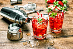 Glass of red drink with ice. Cocktail making bar tools stock image