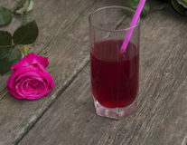 Glass of red drink with a tubule nearby a rose. A still life on a subject drinks Stock Photo