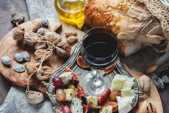A glass of red dry wine and Focaccia Italian bread with cheese and olive oil, sun-dried tomatoes and different kinds of nuts . Sel. Ective focus. A horizontal Stock Photo