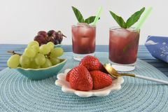 Cold smoothie drink in red berry and grape flavor. Glass of red fruit smoothie drink with ice and fresh mint leaf. Made with strawberry red and green grapes and royalty free stock photography