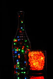 Glass with red garland. Mug and bottle in the light of a garland Royalty Free Stock Photography