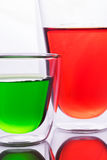 Glass of red and green water Stock Photos