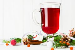 A glass of red hot mulled wine on a light background. Christmas and New Year greeting card. Stock Photography