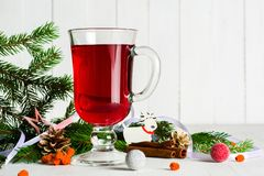 A glass of red hot mulled wine on a light background. Christmas and New Year greeting card. Stock Photo