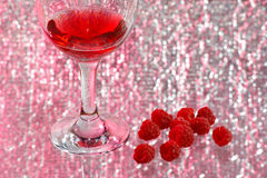 The glass of red liquor and raspberry. The glass of transparent red liquor and raspberry Royalty Free Stock Photo