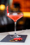 Glass of red martini decorated with chili pepper on stone. On bar counter Stock Images