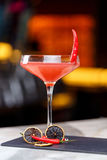 Glass of red martini decorated with chili pepper on stone. On bar counter Stock Photo
