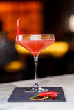 Glass of red martini decorated with chili pepper on stone. On bar counter Royalty Free Stock Image