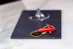 Glass of red martini decorated with chili pepper on stone. On bar counter Royalty Free Stock Photos