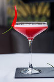 Glass of red martini decorated with chili pepper. On stone on white tablecloth Stock Images