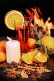 Glass of red mulled wine and flames in background Royalty Free Stock Images