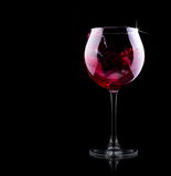Glass of red splashing wine Stock Photos
