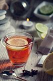Glass with red tea on rustic wooden table. Tea cup with red porcelain teapot in rustic style Royalty Free Stock Photography