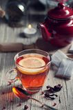 Glass with red tea on rustic wooden table. Tea cup with red porcelain teapot in rustic style Royalty Free Stock Photo
