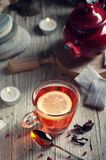 Glass with red tea on rustic wooden table. Tea cup with red porcelain teapot in rustic style Stock Photo
