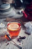 Glass with red tea on rustic wooden table. Tea cup with red porcelain teapot in rustic style Stock Photography