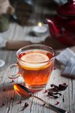 Glass with red tea on rustic wooden table. Tea cup with red porcelain teapot in rustic style Royalty Free Stock Image