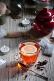 Glass with red tea on rustic wooden table. Tea cup with red porcelain teapot in rustic style Stock Image