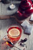 Glass with red tea on rustic wooden table. Tea cup with red porcelain teapot in rustic style Stock Images