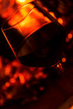 Glass of red vine near fireplace angled close up. Glass of red vine near burning fireplace Royalty Free Stock Photo