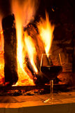 Glass of red vine near fireplace copy space Stock Photography