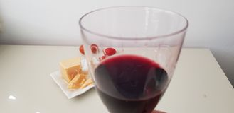 Glass of red vine on white table near cheese and tomatoes stock image