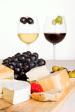A glass of red and white wine. With a cheese board in the foreground Stock Images