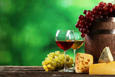 Glass of red and white wine, cheeses and grapes on the brown wooden background Royalty Free Stock Photos