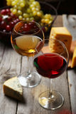 Glass of red and white wine, cheeses and grapes on grey wooden background Stock Images