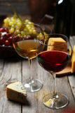 Glass of red and white wine, cheeses and grapes on grey wooden background Royalty Free Stock Image