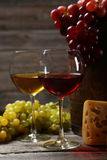 Glass of red and white wine, cheeses and grapes on grey wooden background Royalty Free Stock Photo