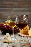 Glass of red and white wine, cheeses and grapes on grey wooden background Royalty Free Stock Images