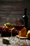 Glass of red and white wine, cheeses and grapes on grey wooden background Stock Photos