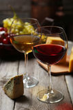 Glass of red and white wine, cheeses and grapes on a grey wooden background Royalty Free Stock Images