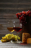 Glass of red and white wine, cheeses and grapes on the grey wooden background Royalty Free Stock Photography