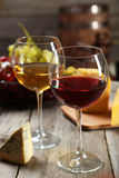 Glass of red and white wine. Cheeses and grapes on grey wooden background royalty free stock photos