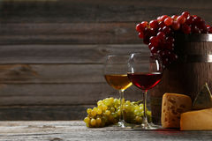 Glass of red and white wine. Cheeses and grapes on grey wooden background royalty free stock photo