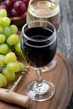 Glass of red and white wine, corkscrew and grapes Stock Image