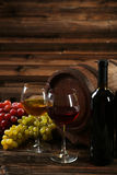 Glass of red and white wine with grapes on the brown wooden background Stock Photos