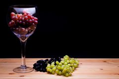 Glass of red win grapes. Grape variety still life. Classic paint. Erly image. Red green and black grape varieties. Summer fruit on farmhouse kitchen table Royalty Free Stock Images